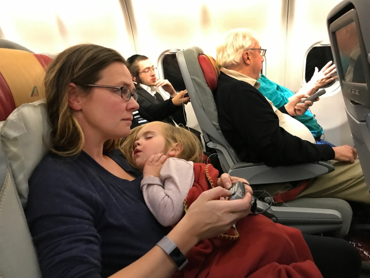 A mother with her sleeping three year old daughter on a flight from New York to Rome. Italy. 22nd October 2017.