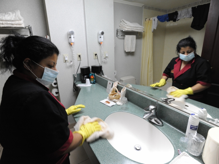 A cleaning woman wears a face mask while she cleans a bathroom at a hotel in San Salvador on May 4, 2009. El Salvador has confirmed its first two cases of swine flu, the country's health minister said Sunday as clinics and public hospitals to stepped up measures to combat the dreaded viral disease.