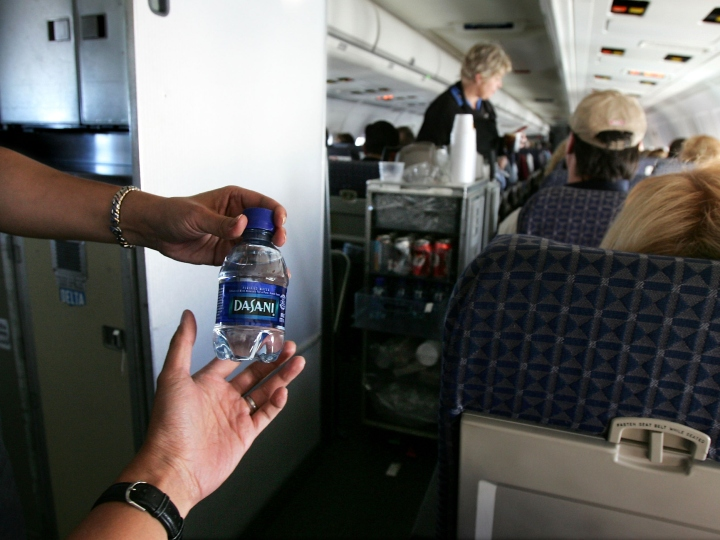 A flight attendant gives out a bottle of water to a passenger on a domestic flight November 19, 2004 in the United States. On flight drinking water quality has been an issue after 20 of 158 randomly selected domestic and international passenger aircrafts that were tested by the EPA did not meet the federal safety standard.