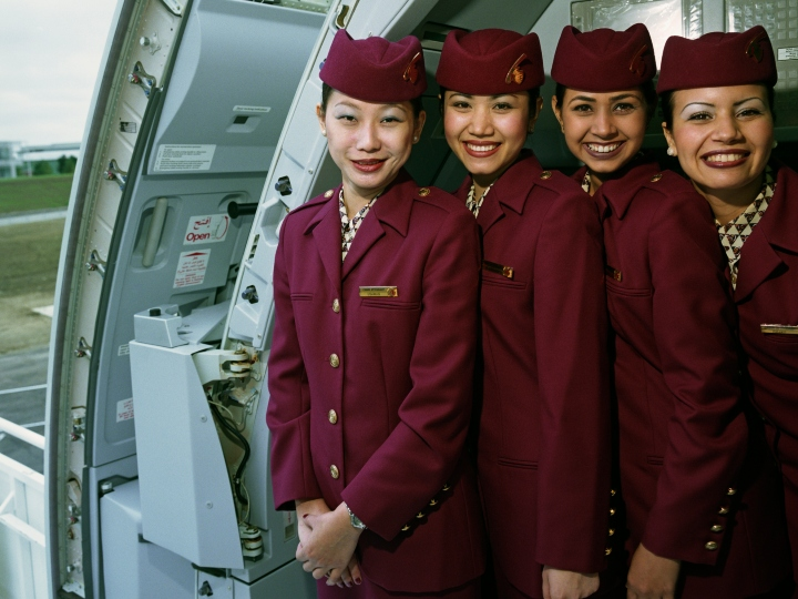 Posing in the open doorway of an Airbus A319CJ Business jet, four female cabin crew members wear the uniforms of Qatar Airways whose airline has made a public relations stop at the Farnborough Air Show to publicise this new model of executive service. Airline stewards and stewardesses are nowadays more commonly referred to as cabin crew or flight attendants. They stand close together with broad grins showing their varied ethnicity. Middle-Eastern airlines generally recruit men and women from western Europe, Asia, Australasia and the Indian sub-continent dependent on routes and aircraft type. Picture from the 'Plane Pictures' project, a celebration of aviation aesthetics and flying culture, 100 years after the Wright brothers first 12 seconds/120 feet powered flight at Kitty Hawk,1903.