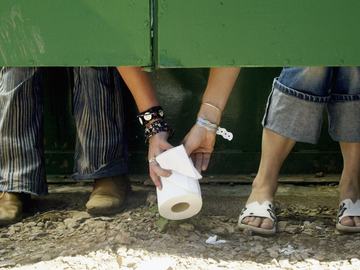 Two festival-goers pass a roll of toilet paper between toilet cubicles, during the 2004 Glastonbury Festival on June 25, 2004 at Worthy Farm, Pilton, Somerset, England. The music festival spans over 3 days and runs until June 27.