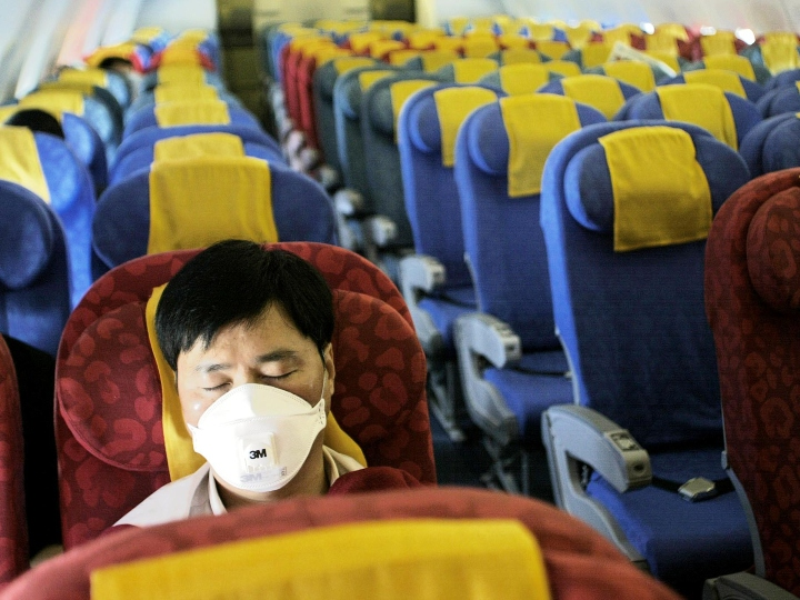 A passenger sleeps wearing a mask to protect against SARS on an almost empty Dragonair flight from Hong Kong to Beijing 21 May 2003. Dragonair, Hong Kong second carrier has seen passenger volumes plummet 75 percent since the outbreak of the disease known as Severe Acute Respiratory Sydrome (SARS) in March.