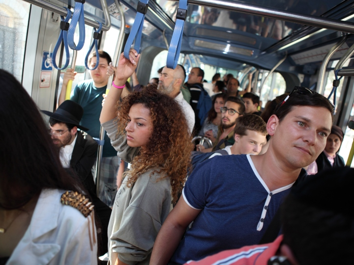 A crowd of passengers, men and women, Jews and Arabs, Orthodox and secular traveling on the Light Train or Light Rail, Jerusalem, Israel, October 6, 2014
