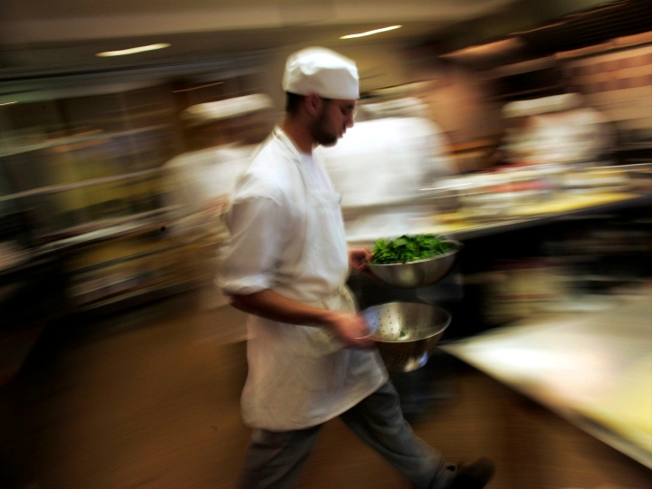 """A culinary student rushes through the kitchen with greens during a class for aspiring professional chefs at The Institute of Culinary Education in New York City February 1, 2007 in New York City. A boom in all things food, including the popularity of television chefs and cooking shows, is increasing demand for cooking classes for amateurs and aspiring professionals alike. Brian Aronowitz, who works at ICE, says that enrollment for all classes is up, and that the famous cooking school is 24 hour a day facility, with classes, cooking shows, and clean up going on around the clock. """"Cooking is the new post-grad type of career,"""" Aronowitz says."""