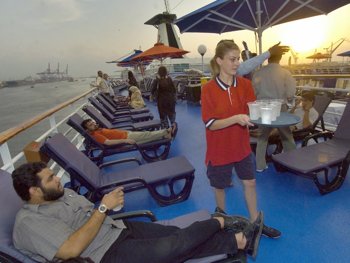 A foreign crew member serves drink to passengers of the Pakistan-Dubai luxury liner Dream Cruise at Karachi harbor, 07 November 2006. The Gulf Dream Cruise vessel weighs 23,000 tonnes and has a length of 196 metres, has 550 spacious rooms with a capacity to carry 1,250 passengers besides 400 crew members and will run a weekly ferry service between Dubai and Karachi.