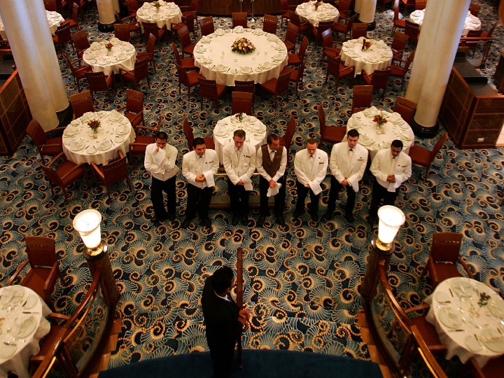 Waiters gather in the Britannia Restaurant aboard the Queen Mary 2 Commodore Warwick cruise ship on its maiden call to the Port of Los Angeles February 22, 2006 at the Los Angeles, California area community of San Pedro. The QM2, the most expensive and largest ocean ship ever built, had to be backed into the harbor because its 1,100 foot length prevented it from reaching port in the usual way.