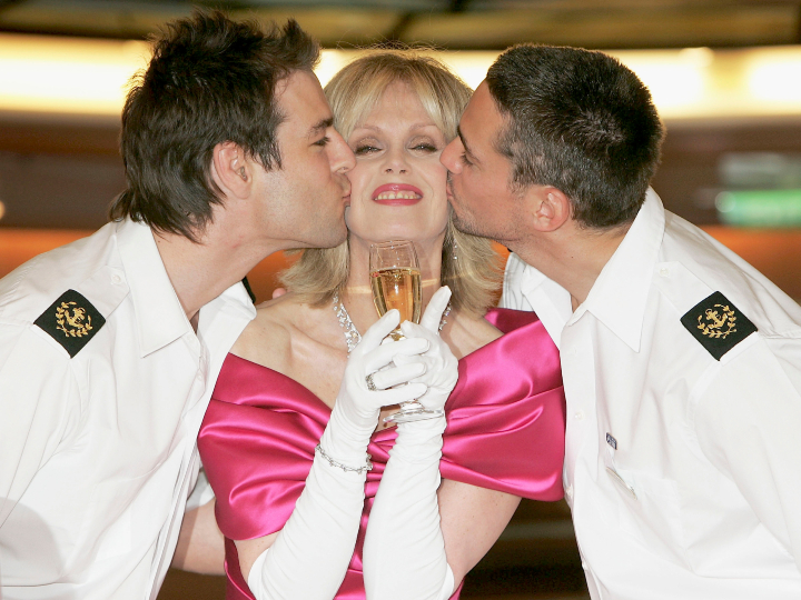 "Actress Joanna Lumley is kissed by two sailors ahead of officially naming Princess Cruises' latest super-liner ""Sea Princess"" by smashing a bottle of Bollinger against the vessel at Western Docks, Ocean Village on May 26, 2005 in Portsmouth, England."