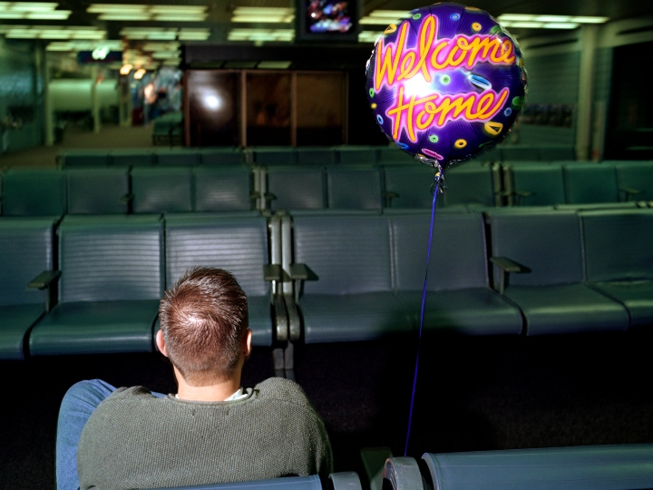 Late at night, in a gloomy arrivals gate at Chicago O'Hare airport, a young man sits patiently on his own awaiting the arrival of his girlfriend after a holiday in Asia. It is the last flight to land and a helium balloon floats on a string bearing the words 'Welcome Home', a popular gesture for relatives in airports around the world, each having their own cultural way of showing affection for arriving family members after long absences. The balloon stands still, the only colour amid the drab interior of this sprawling airport hub. Picture from the 'Plane Pictures' project, a celebration of aviation aesthetics and flying culture, 100 years after the Wright brothers first 12 seconds/120 feet powered flight at Kitty Hawk,1903.